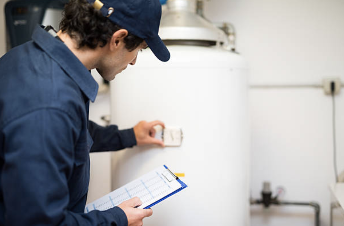 technician reading dial of water heater tank